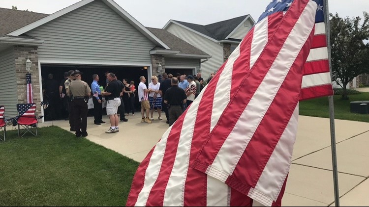 A crowd gathered in Sydney Dutton's garage for her annual flag giveaway