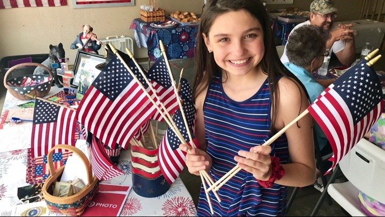 Sydney Dutton holds some of the flags she distributed in honor of her father