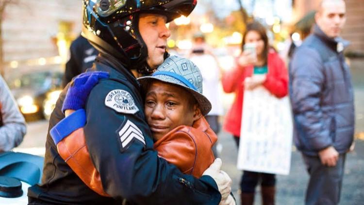 In this Tuesday, Nov. 25, 2014 photo, Portland police Sgt. Bret Barnum, left, and Devonte Hart, 12, hug at a rally in Portland, Oregon. (Photo: Johnny Nguyen via MSNBC.com via Associated Press)