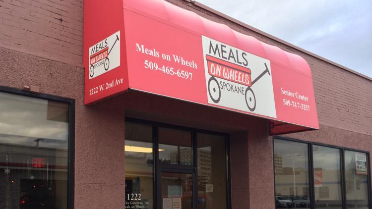 Bank employees help wash graffiti off Spokane Meals on Wheels building