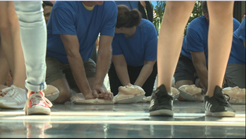 KREM 2's Tom Sherry helps guide Hands-Only CPR class