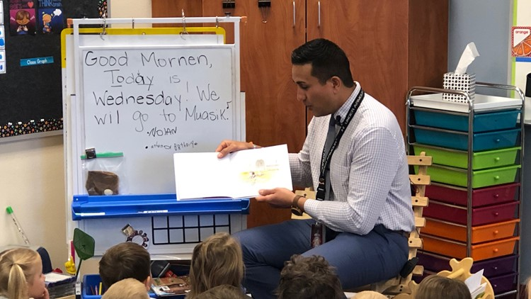 Crimson Point Elementary Principal Brandon Crusat visiting a classroom, reading to his students.