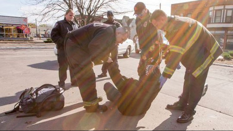 A man is helped off the ground, suspected of being on KD, a local drug involving bug spray being applied to a cigarette of some kind, in Indianapolis, last November.
