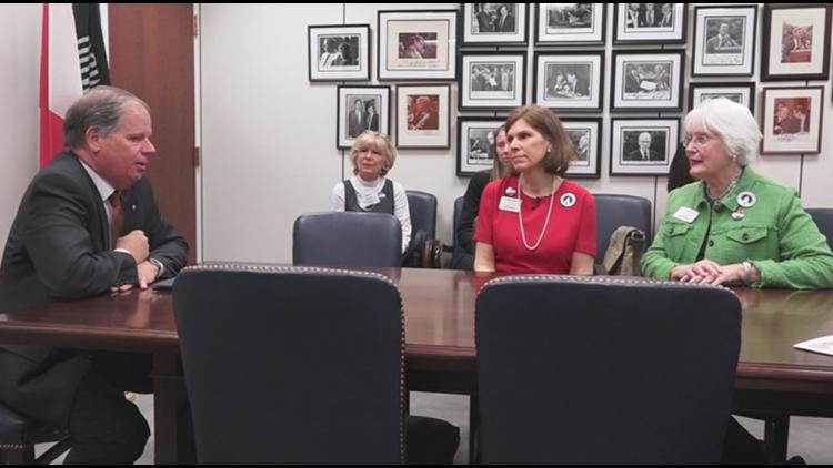 Surviving military spouse Kathy Thorp and MOAA member Anne Hartline meet with Sen. Doug Jones, D-Alabama